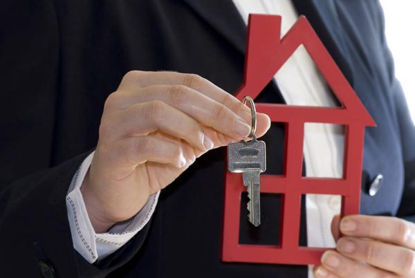 家の模型と鍵を持つビジネスマン