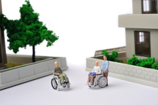 車いすに乗る高齢者と住宅街